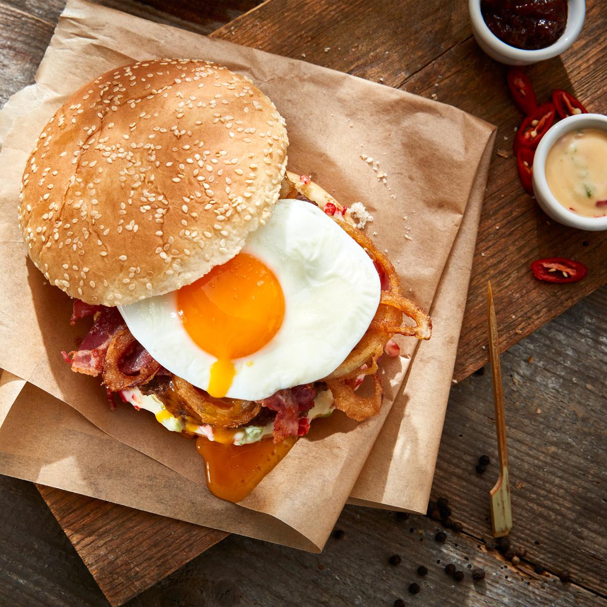 Leckerer Beefburger mit Spiegelei auf Holz serviert